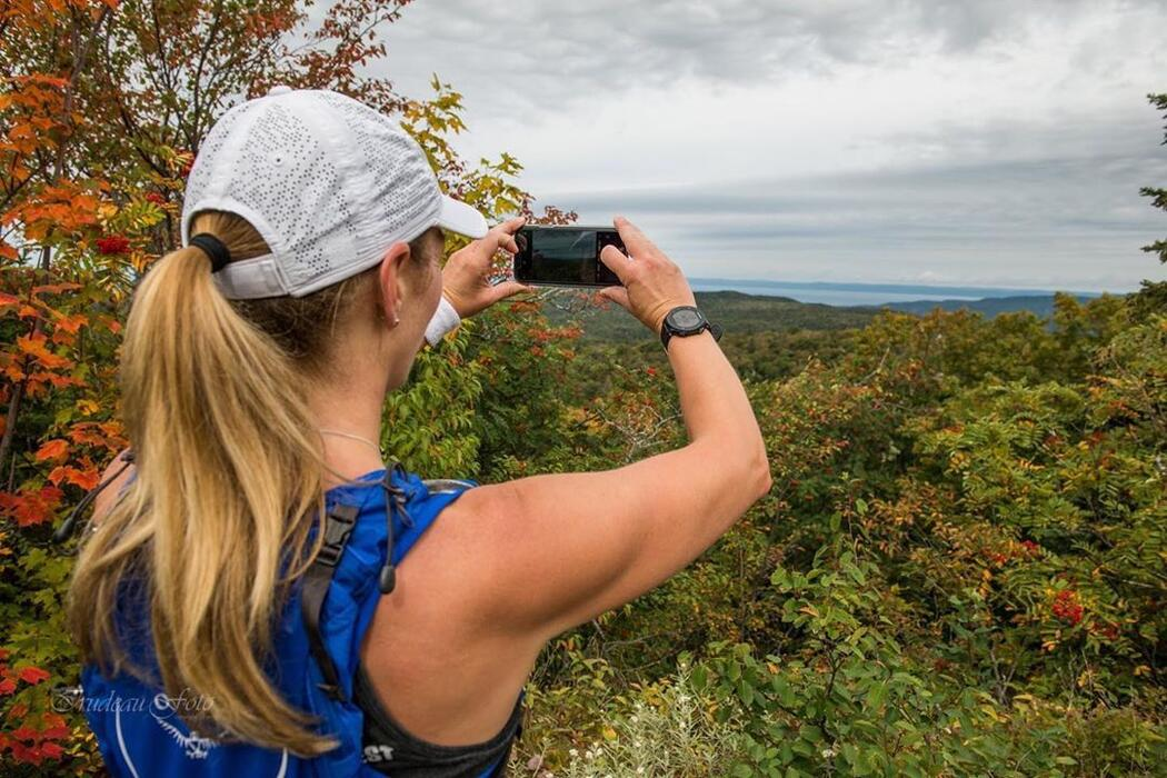 Woman in baseball cap with blond ponytail taking a picture of view with phone.