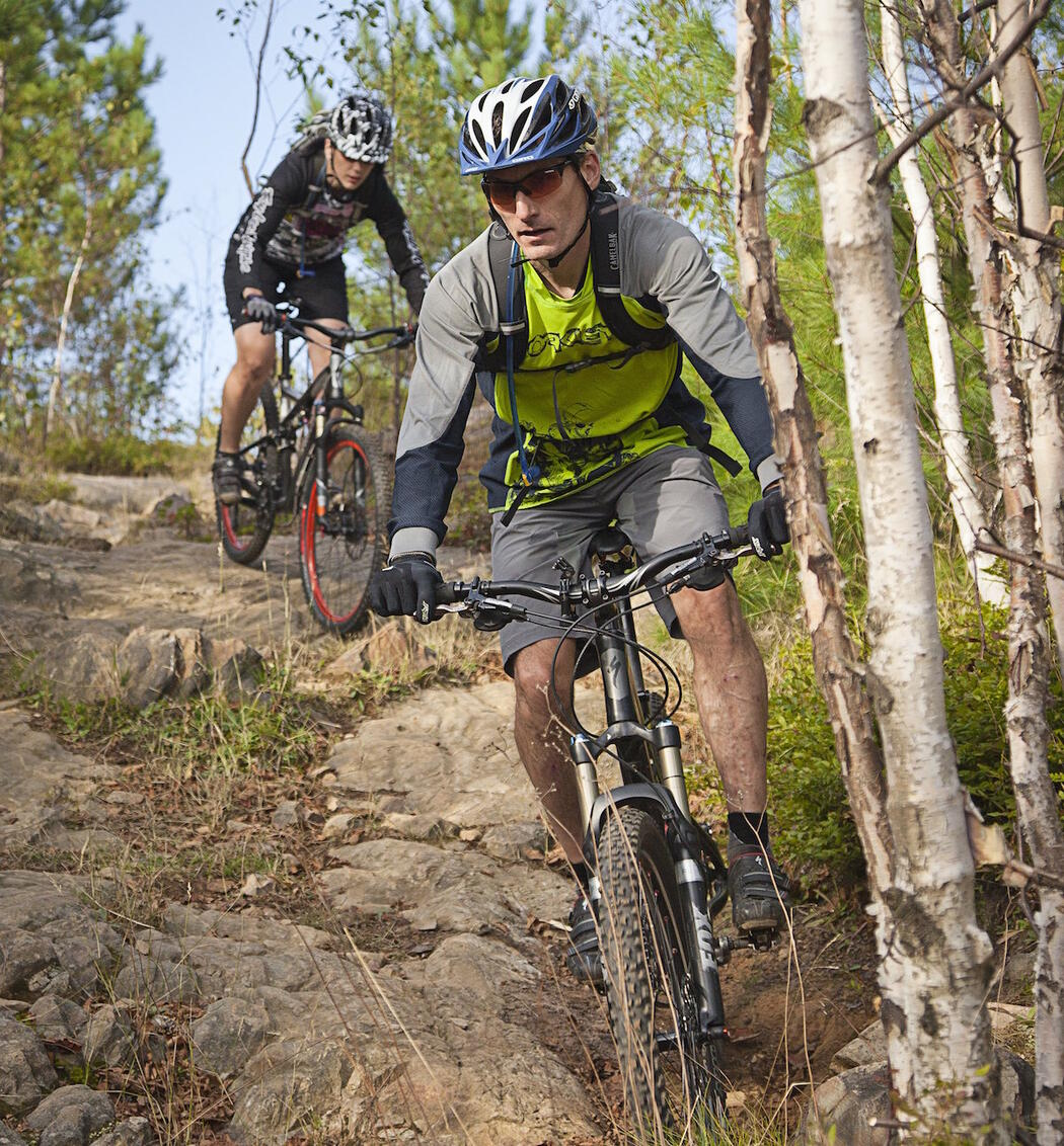 Mountain bikers riding on rough rocky trail.
