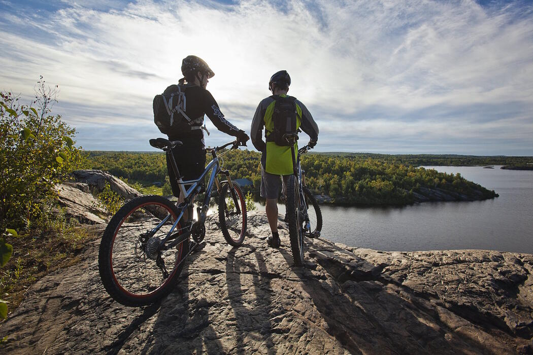 Two cyclists standing with bikes on a rocky lookout overlooking a lake.