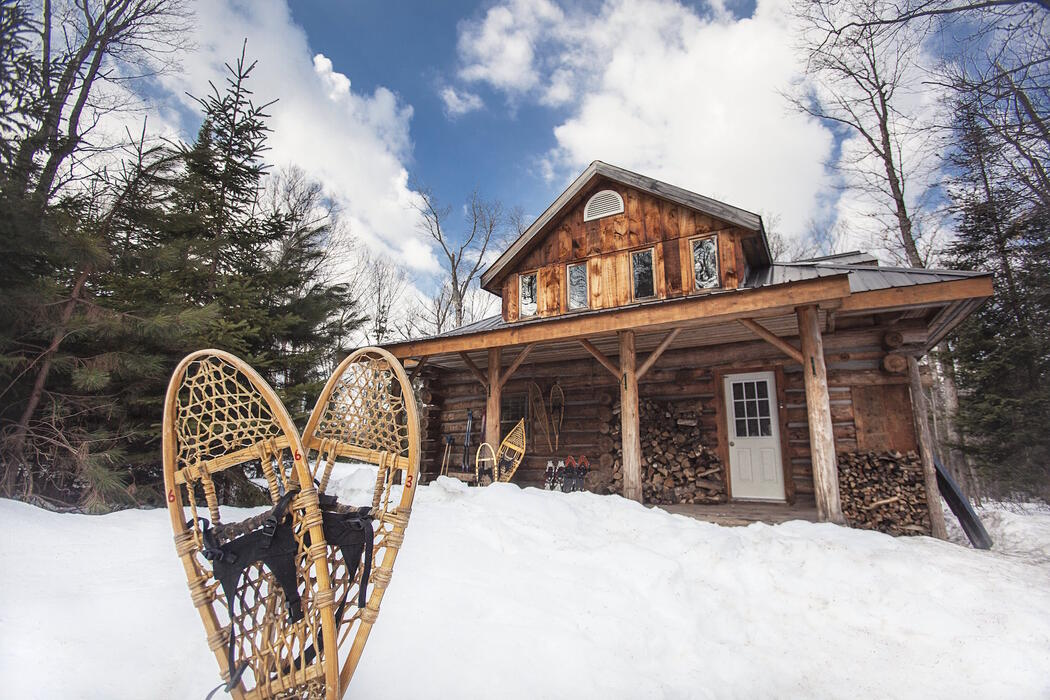 Log cabin lodge in snowy winter with a pair of snowshoes in front.