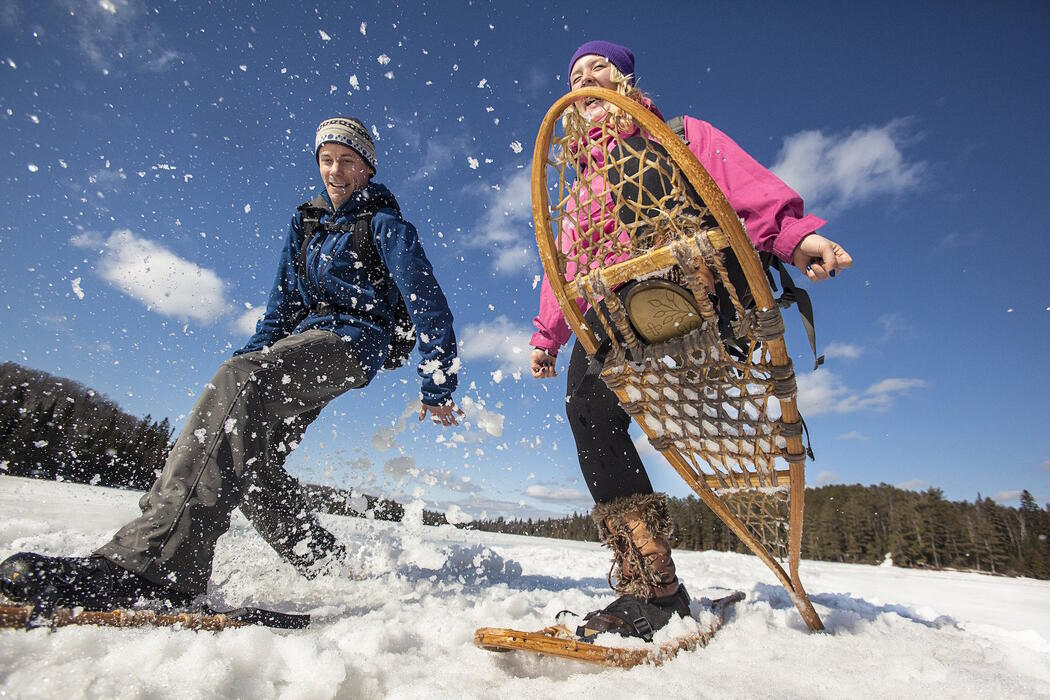 Two people snowshoeing on a lake.