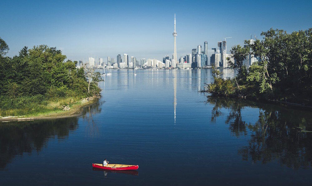 Red canoe in sheltered bay on Centre Island with CN Tower in background