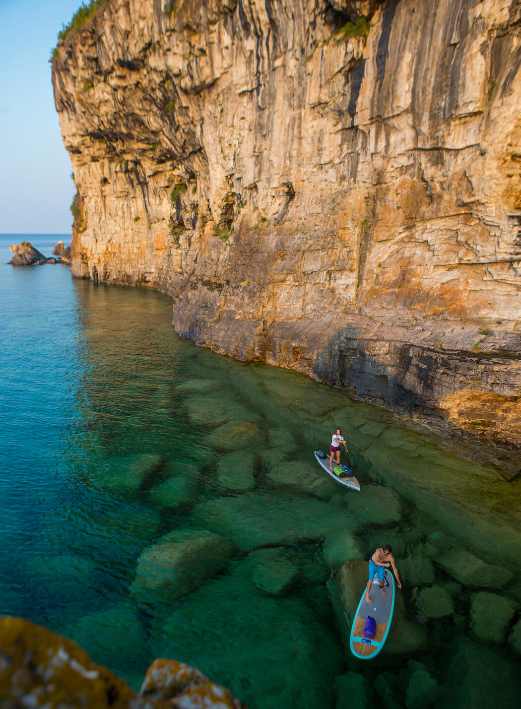Two people stand-up paddle boarding along side tall cliffs