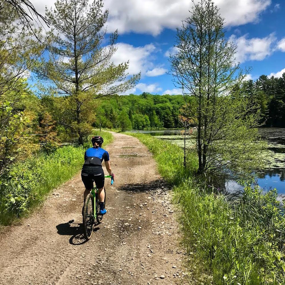 Woman riding a bicycle on a gravel road beside a pond