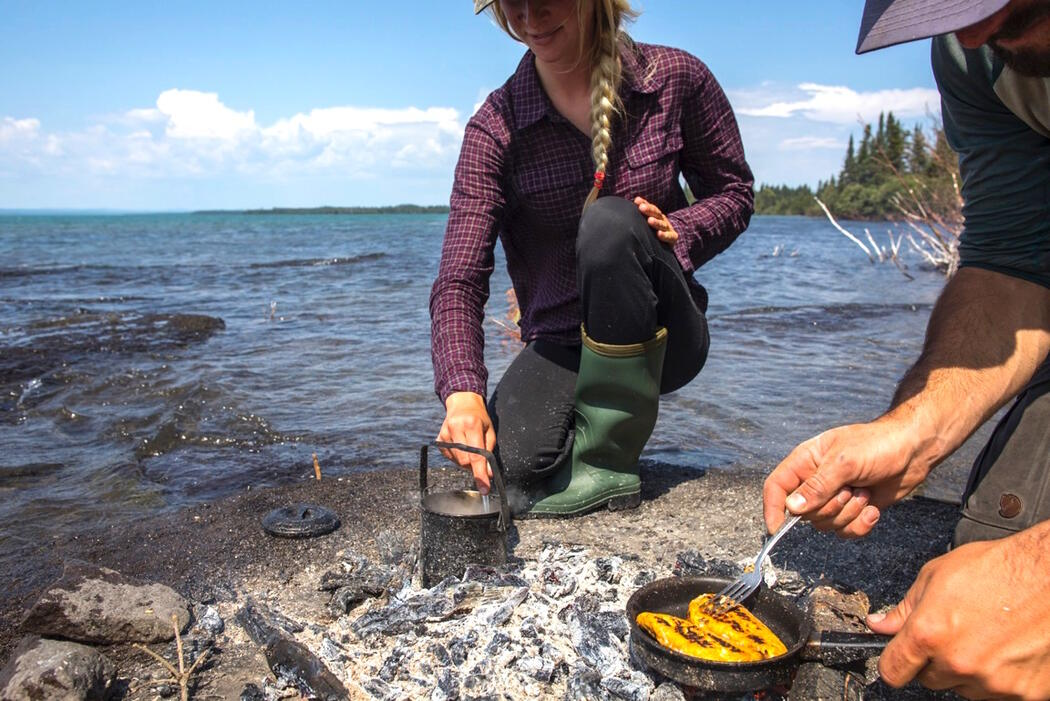 Man and woman cooking fish in a frypan over an open fire