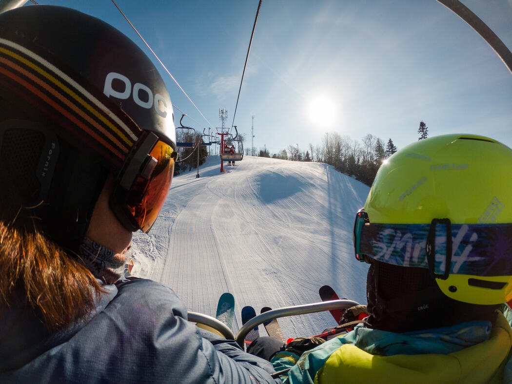 View of back of two people sitting on a chair lift.
