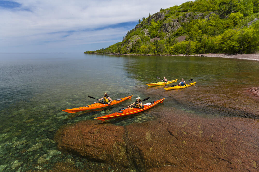 Four kayakers paddling over crystal clear water along rocky coast