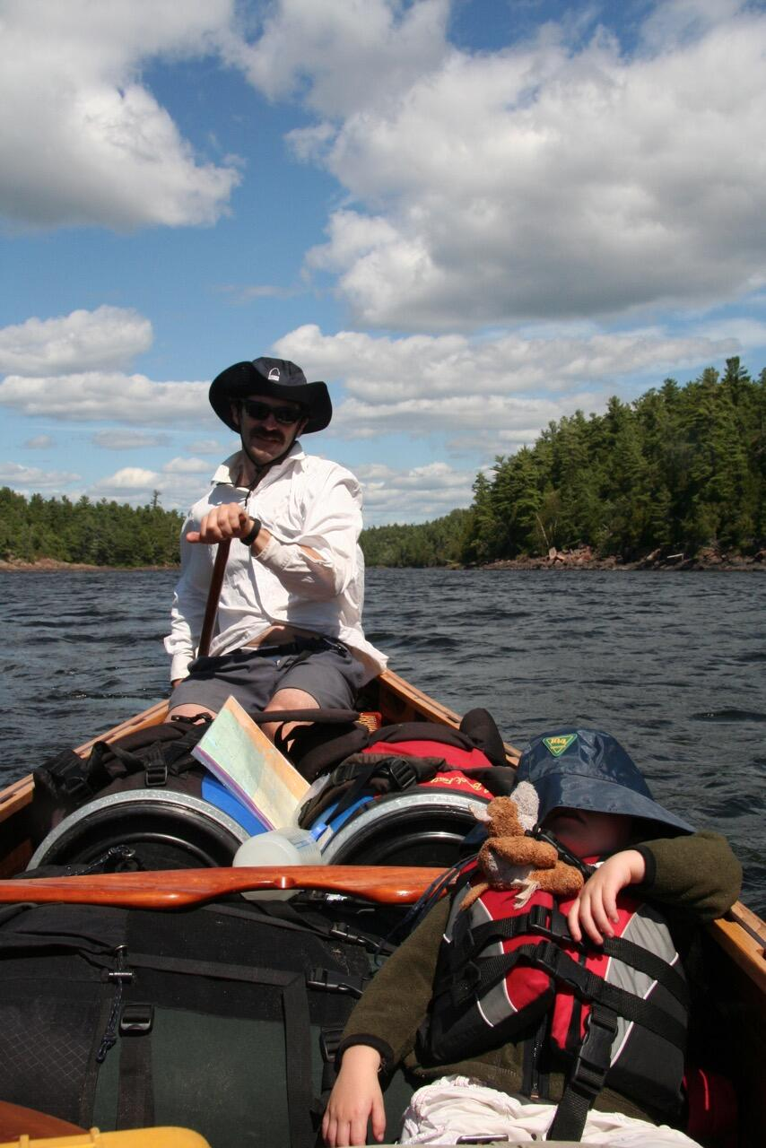 Man paddling a canoe with child sleeping in centre of canoe