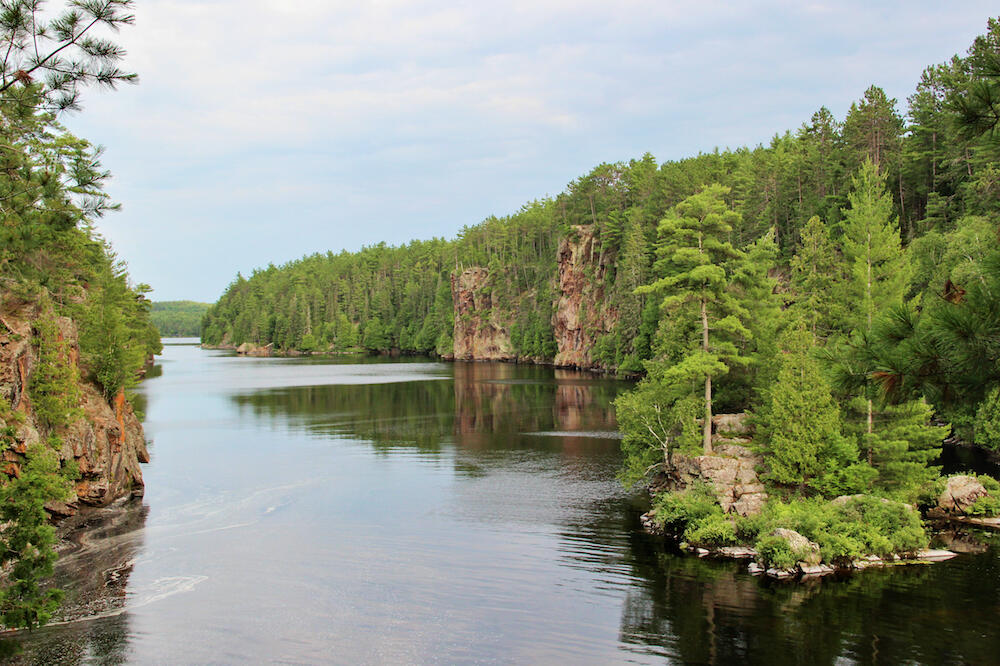 Looking down a river with large rock cliffs on either side.