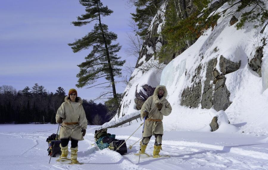 Man and woman in traditional winter gear pulling toboggans on snow-covered lake beside a rock face