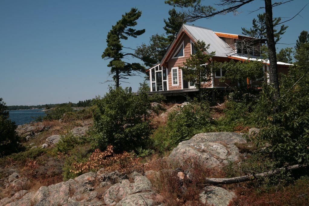 Small cottage perched on smooth rocks with a few pine trees.