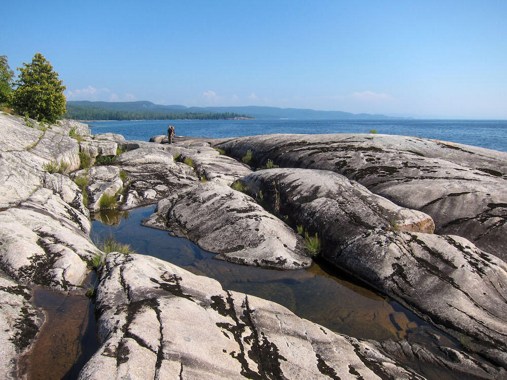 Hiker in distance on flat rocky shoreline on Lake Superior