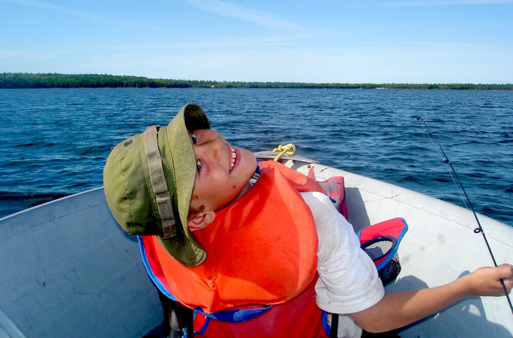 Young boy in lifejacket in fishing boat on a lake