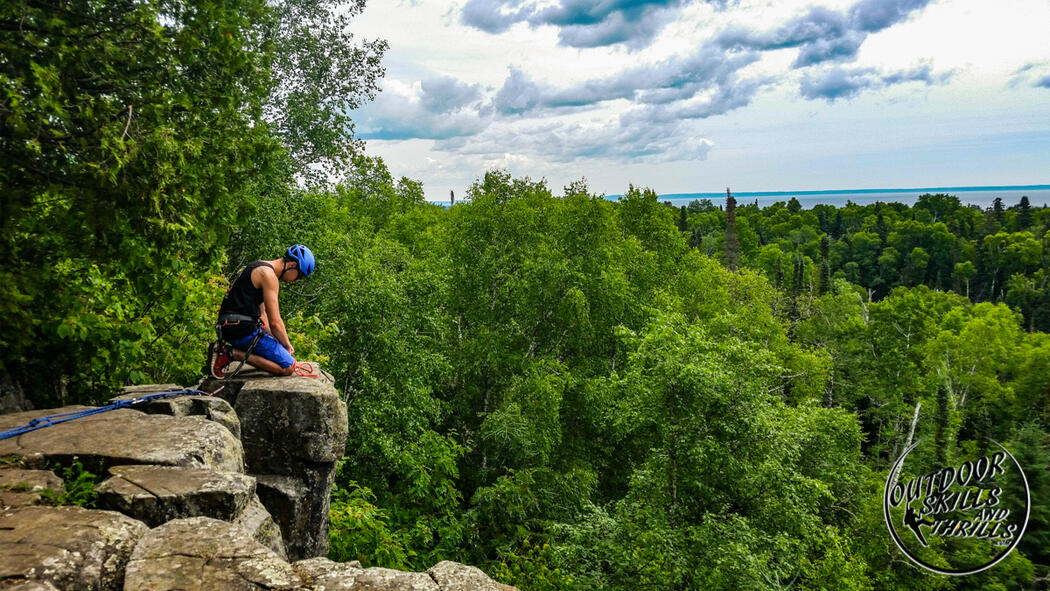 Person kneeling on edge of rock cliff, after climbing it.