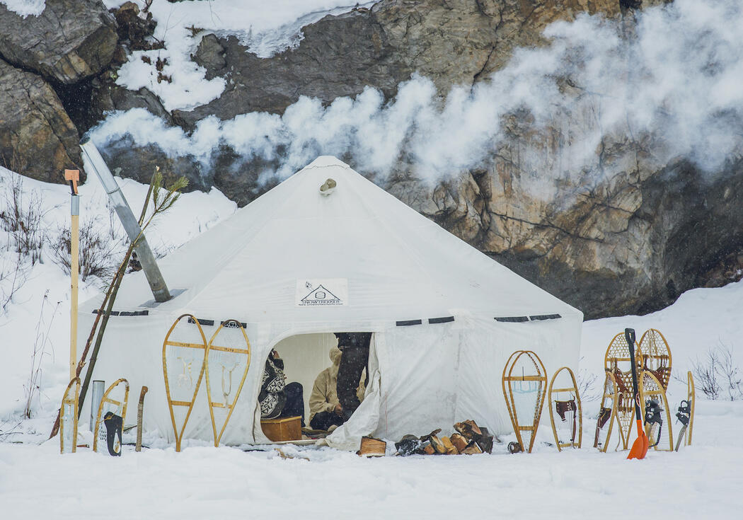 Large white canvas tent with smoke coming out chimney, snowshoes standing in snow