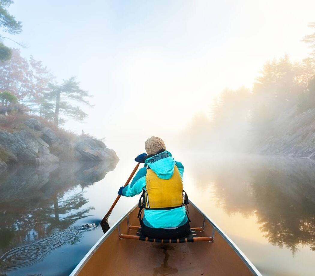Person wearing a jacket and life jacket paddling in bow of a canoe.