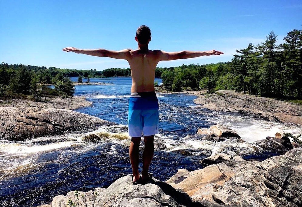 Young man standing with his arms outstretched, overlooking the Moon River.