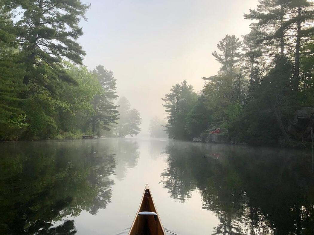 Bow of canoe travelling on a misty river.