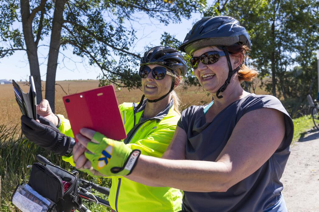 Two woman taking selfies while standing over their bicycles.