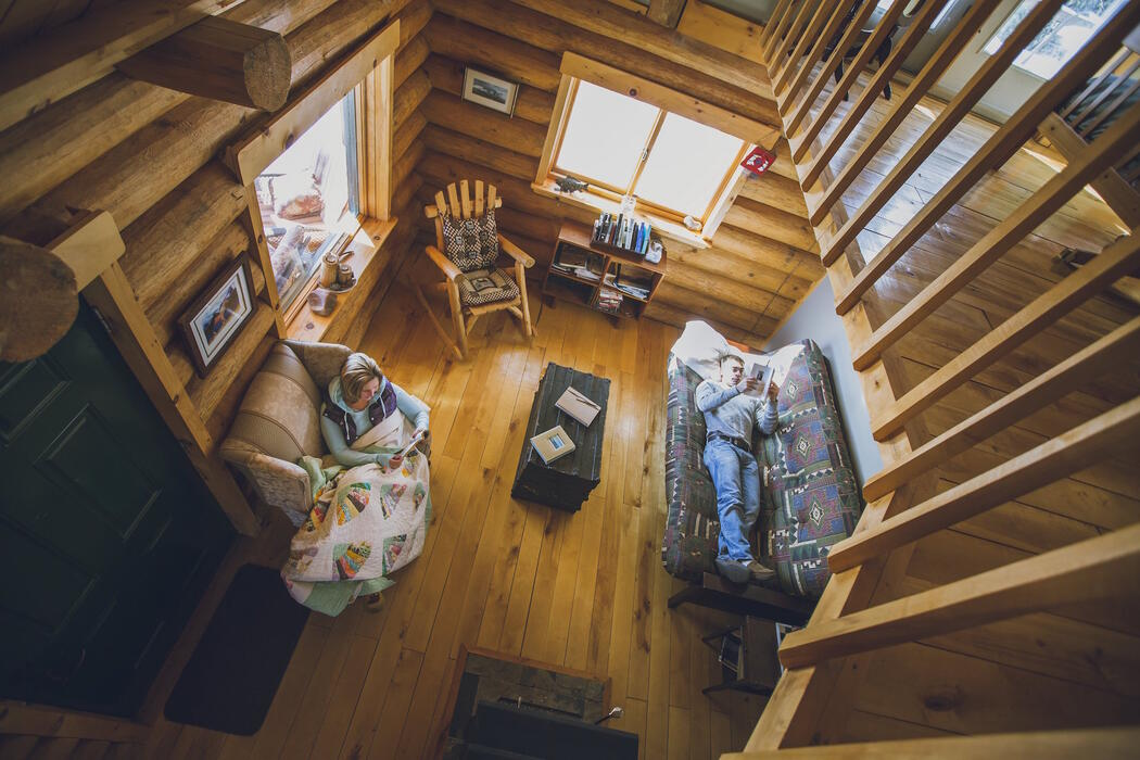 Looking down from a loft at two people relaxing in a cozy log cabin.