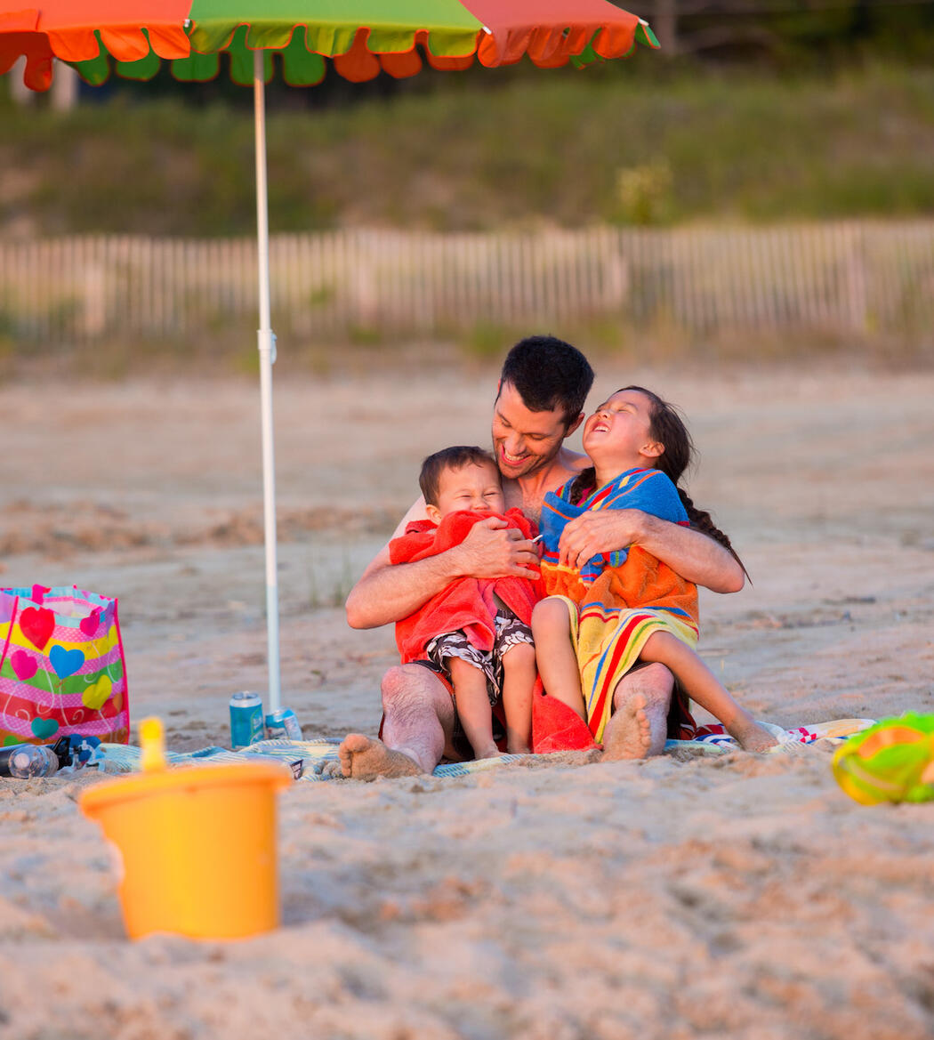 Man sitting on a beach under an umbrella hugging two laughing kids.