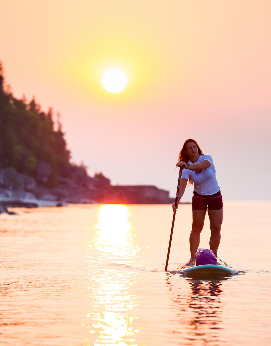 Strong woman stand-up paddle boarding in front of warm sunset