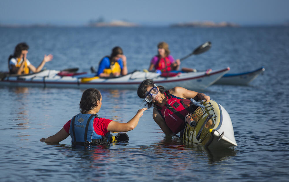 Woman in a kayak about to do a wet exit with a guide beside her