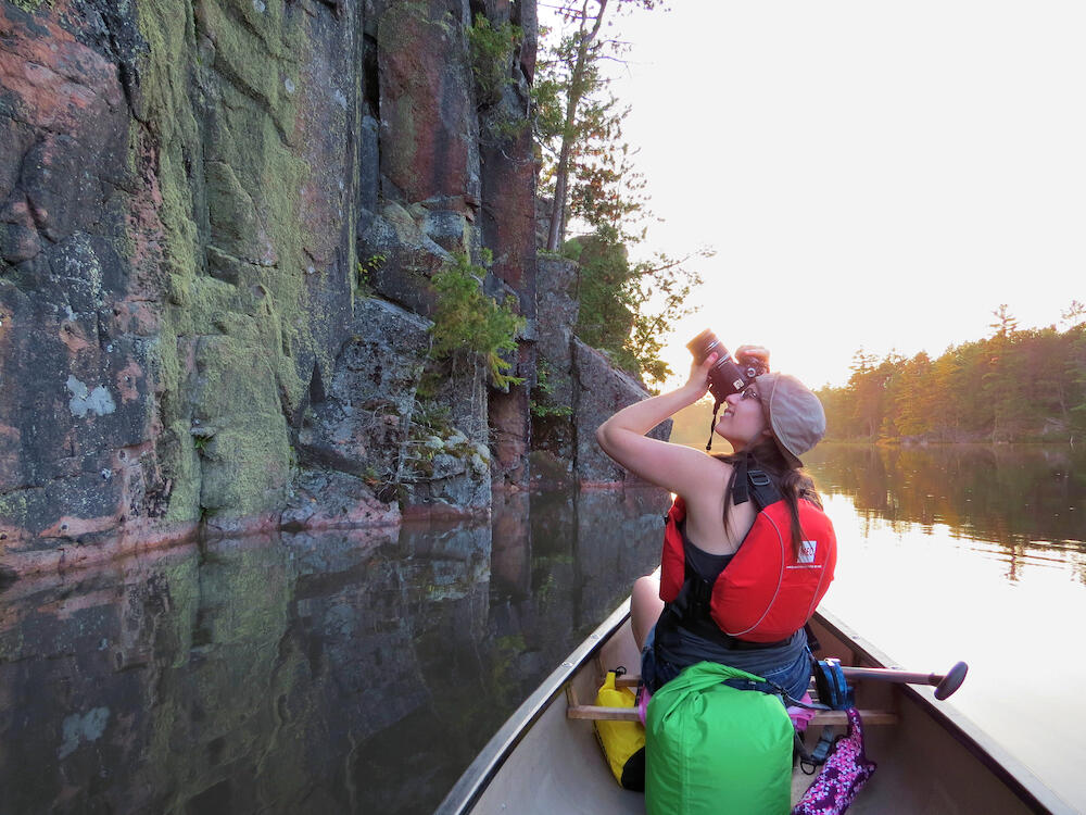 Woman photographing rocky cliffs while in a canoe on a river.