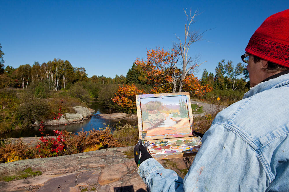 Man painting scene of rocks, trees and water in Killarney