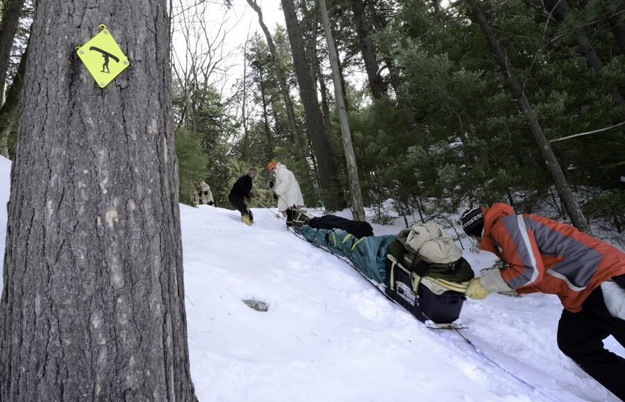 Man pushed loaded toboggan up a snow-covered hill beside tree with portage sign