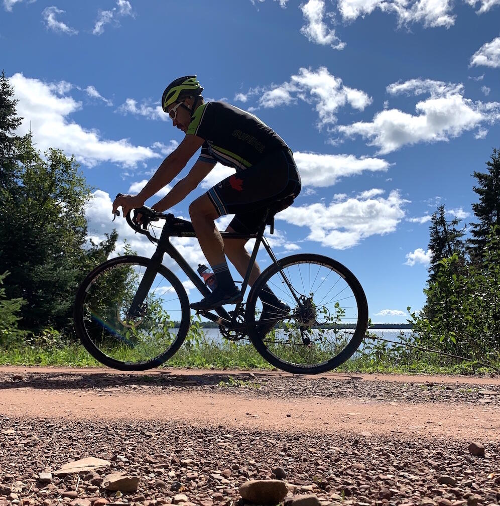 Man on a mountain bike riding on a gravel road with a lake and clouds in background.