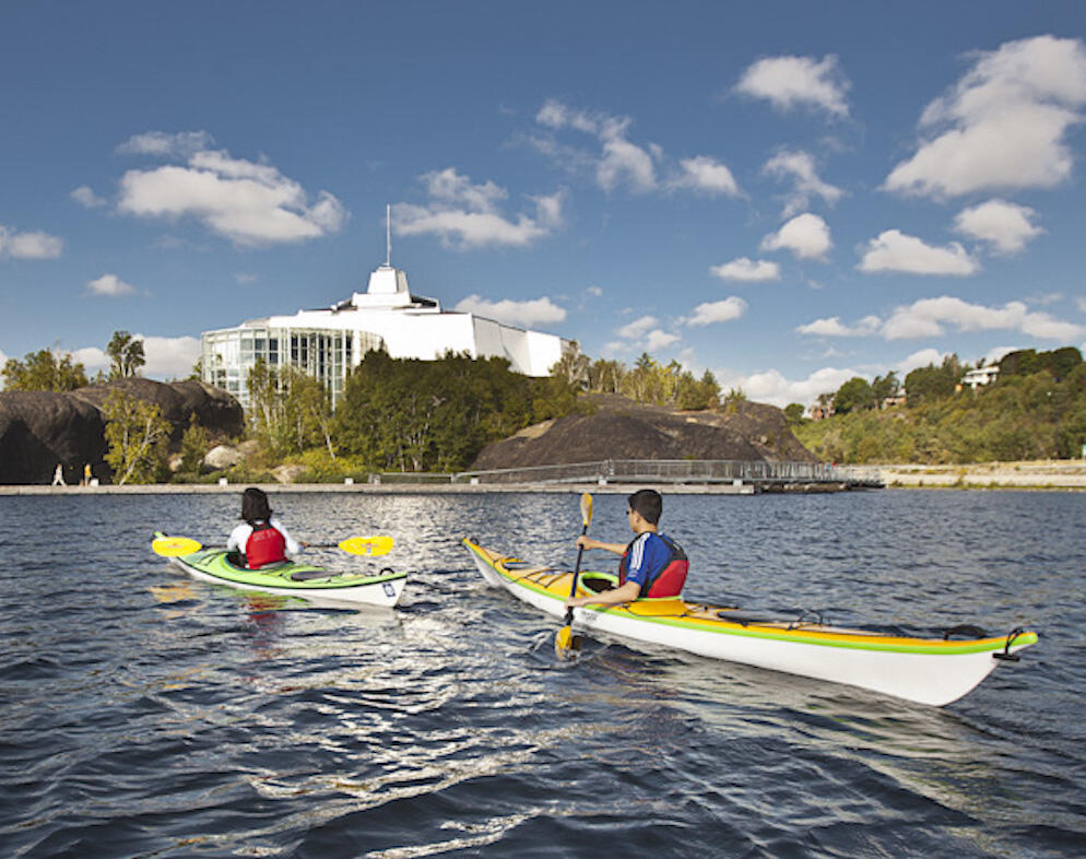 Two kayakers paddling in front of Science North