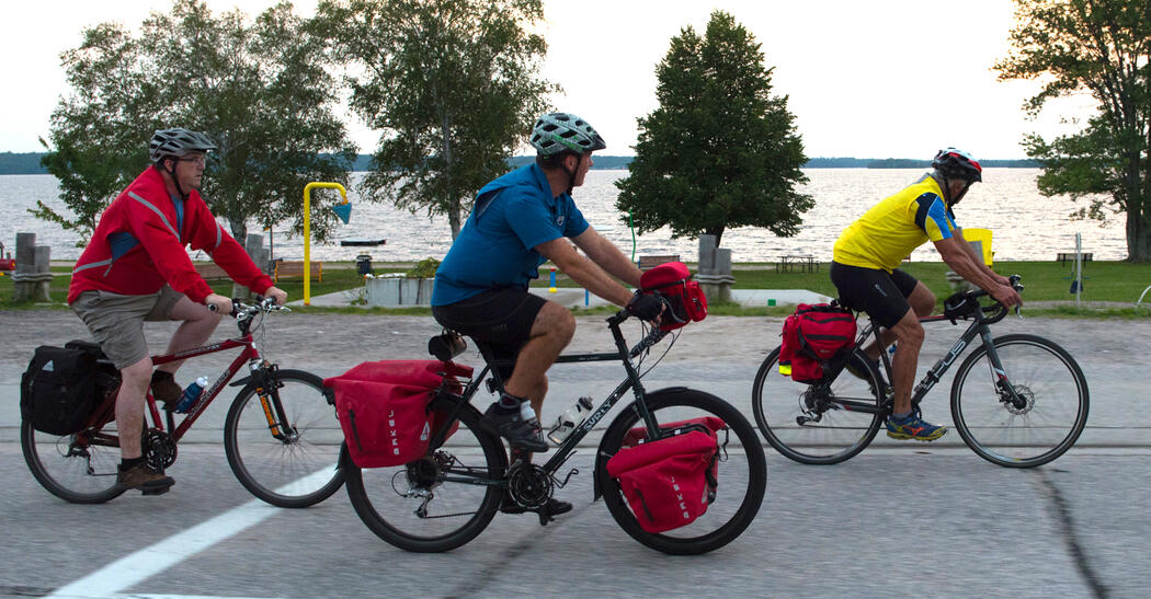 Three cyclists riding bikes with cycling packs.