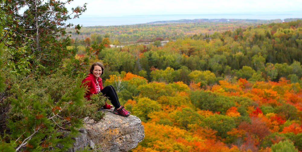 Woman sitting on a rock ledge overlooking scenic fall foliage