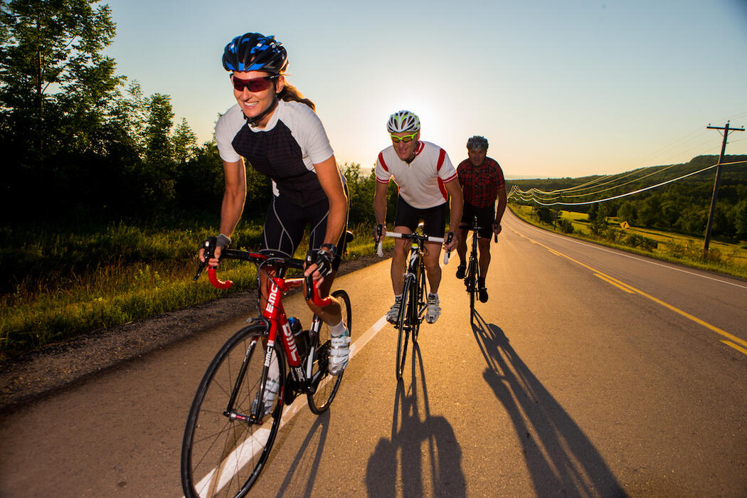 Three cyclists riding on paved road with sunset in background