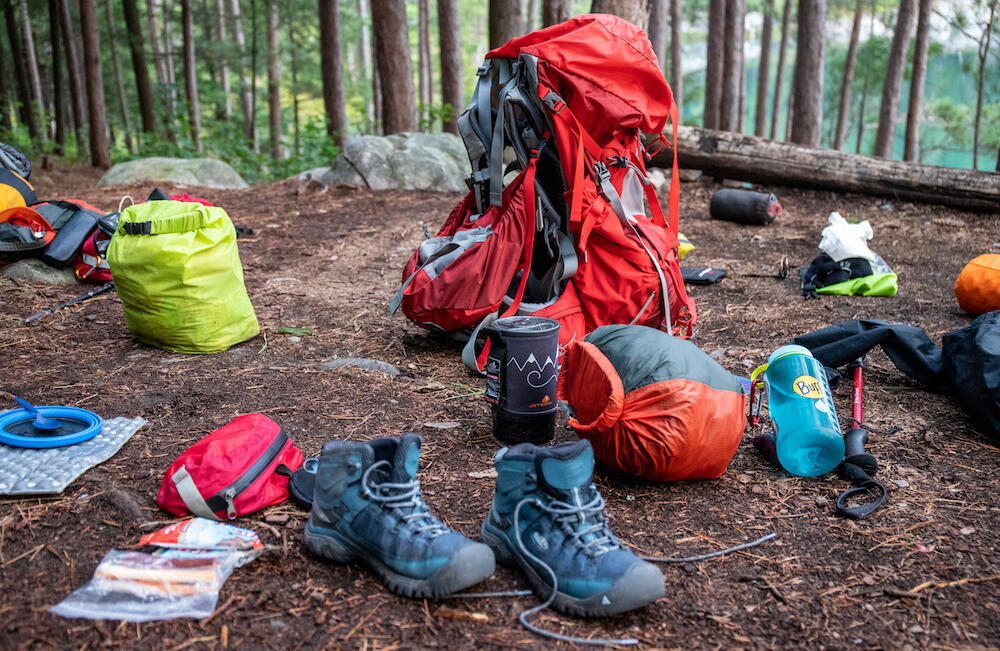 Boots, plates, pack, dry bags and other gear on a campsite.