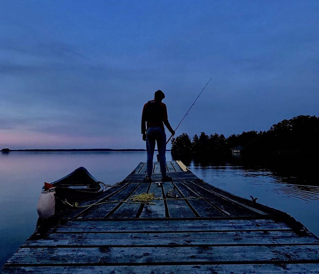 Man standing at the end of a dock fishing at twilight.