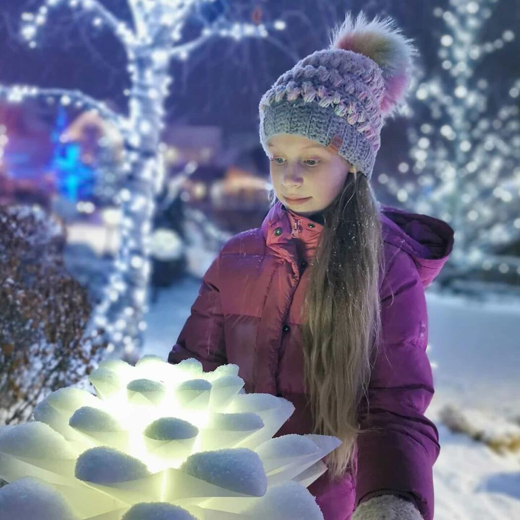 Young girl in winter jacket and hat looking at glowing lights.