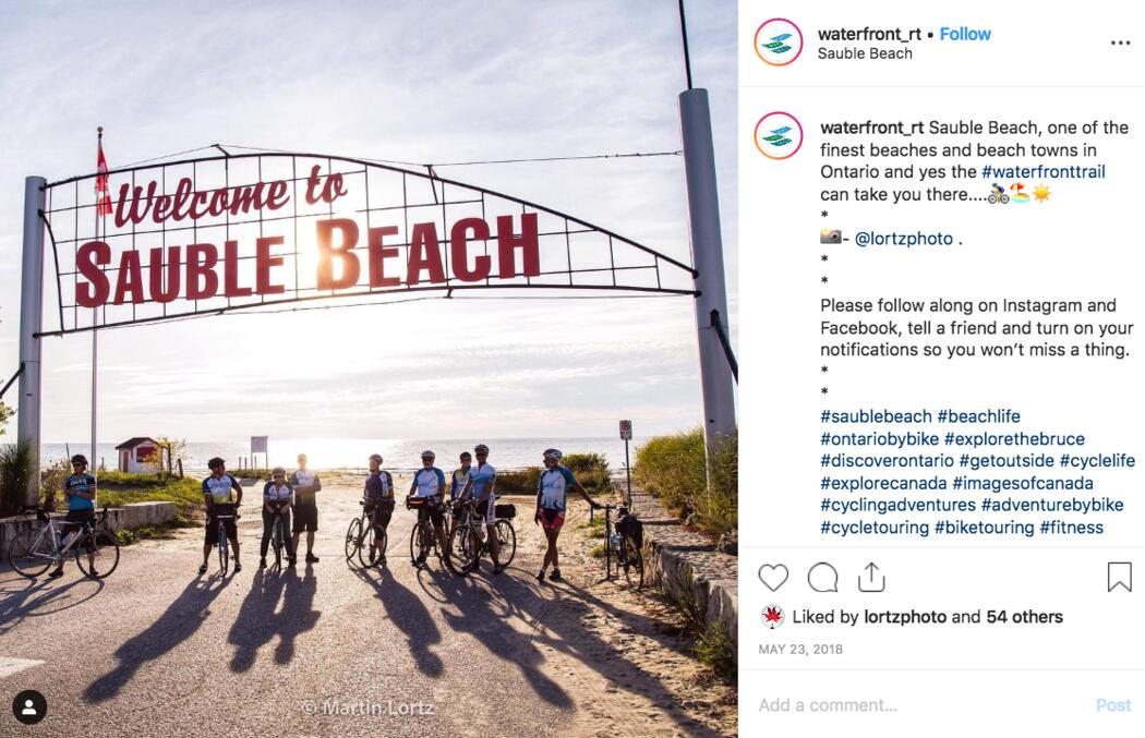 Instagram post showing cyclists under the Welcome to Sauble Beach sign