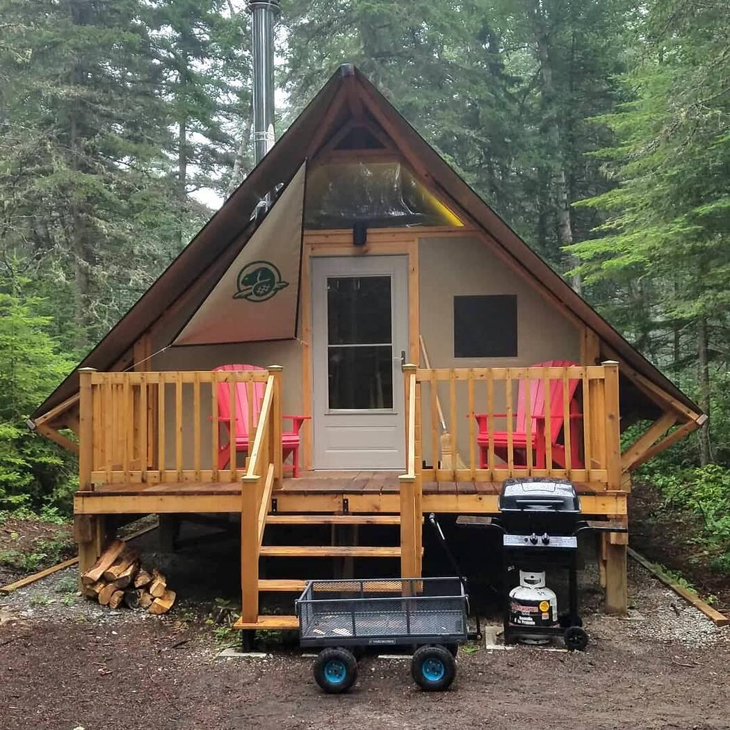 Wooden A-frame cabin with front deck.