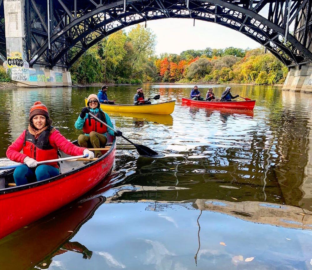 Three canoes paddling under a metal bridge arch.