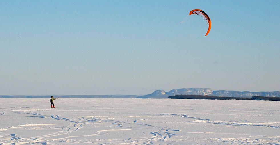 Person snowkiting on a frozen lake.