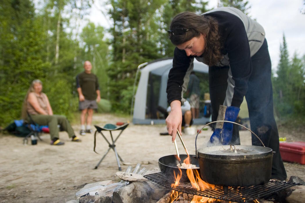 Woman cooking over a campfire.
