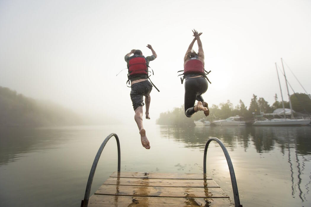 Two people in life jackets jumping off end of dock into water on a misty morning.