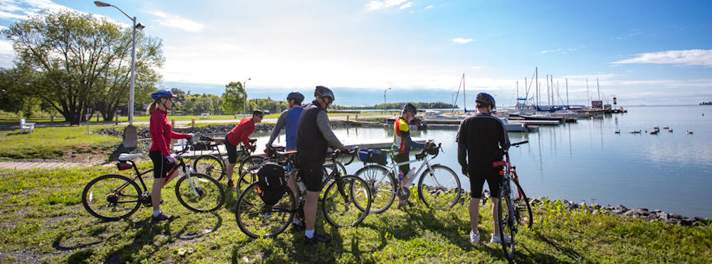 Group of cyclists standing with bikes looking a beautiful harbour with sail boats