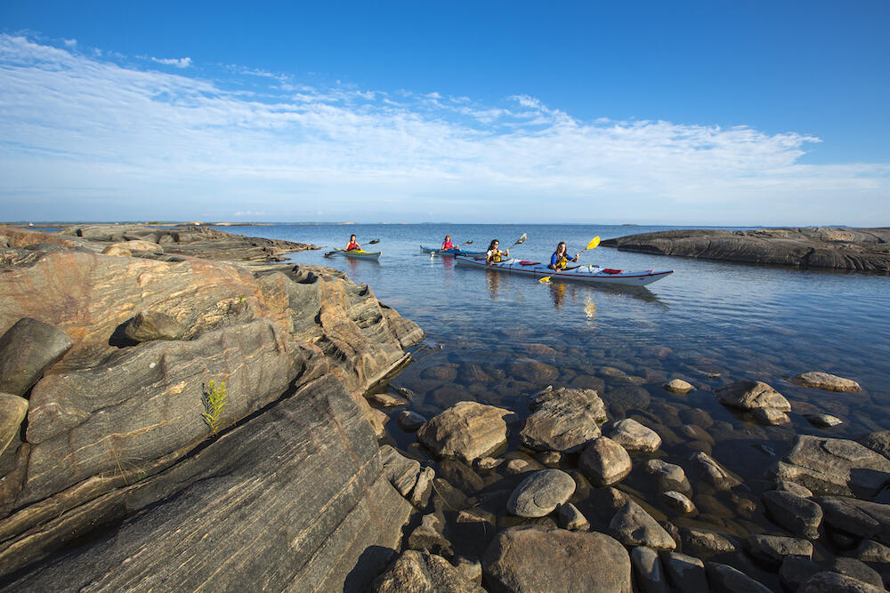 Three kayakers paddling through a sheltered bay surrounded by smooth rock.