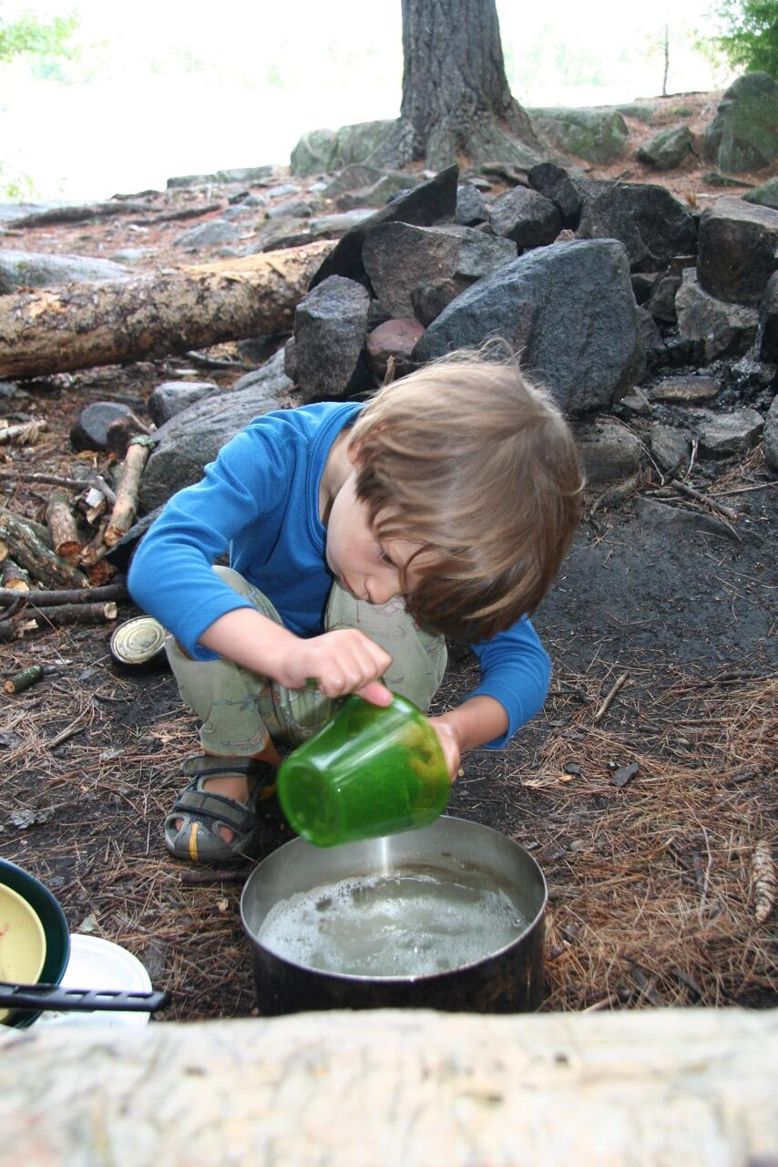 Young boy washing dishes at a campsite