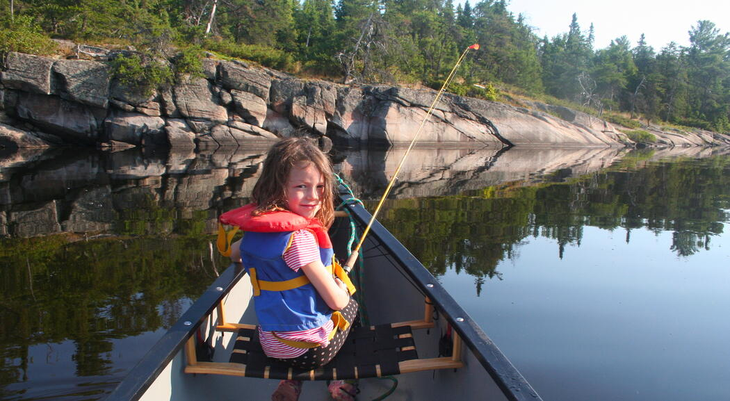 Young girl in canoe fishing on a calm river.