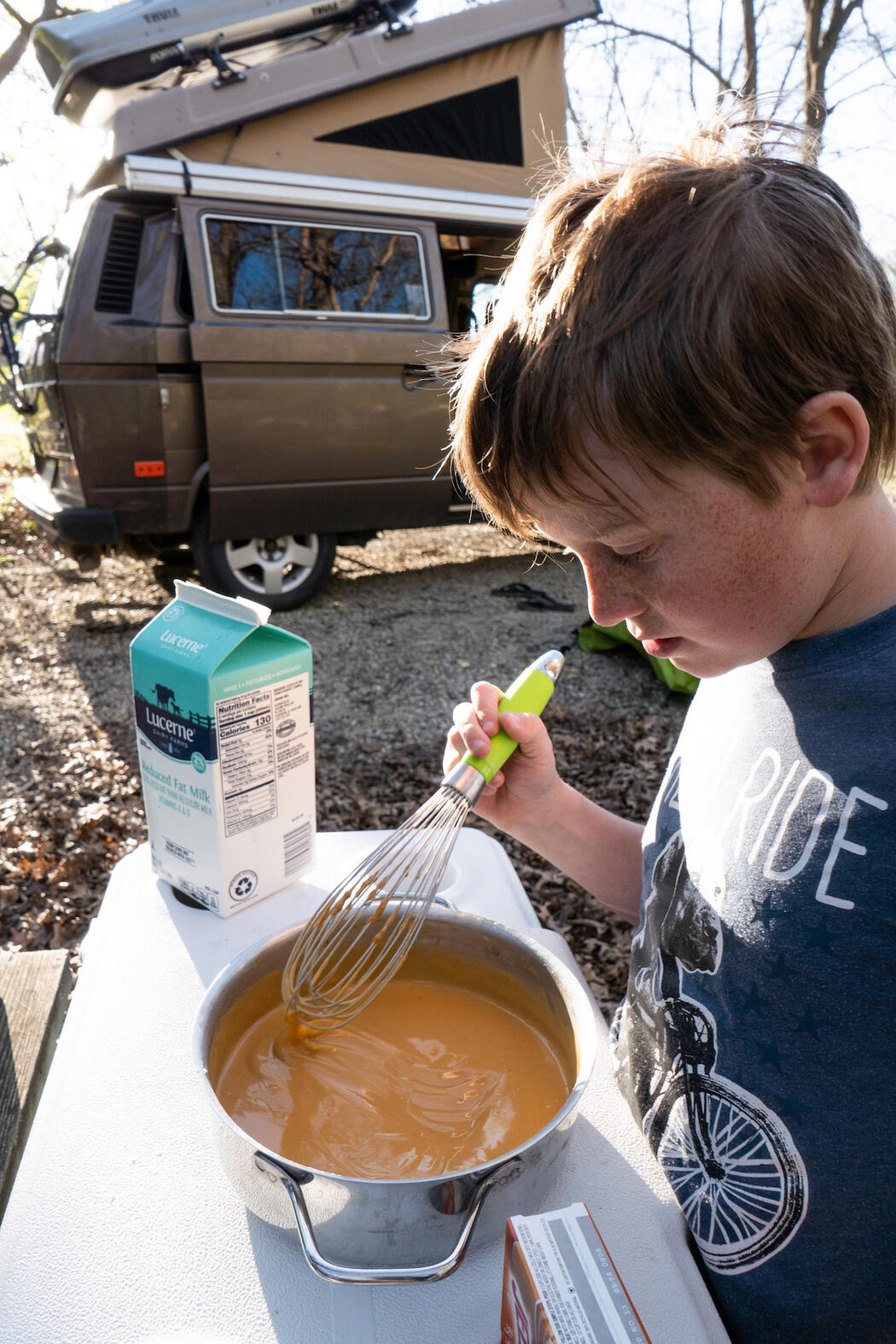 A young boy stirring a pot of pudding with a camper van parked in background.