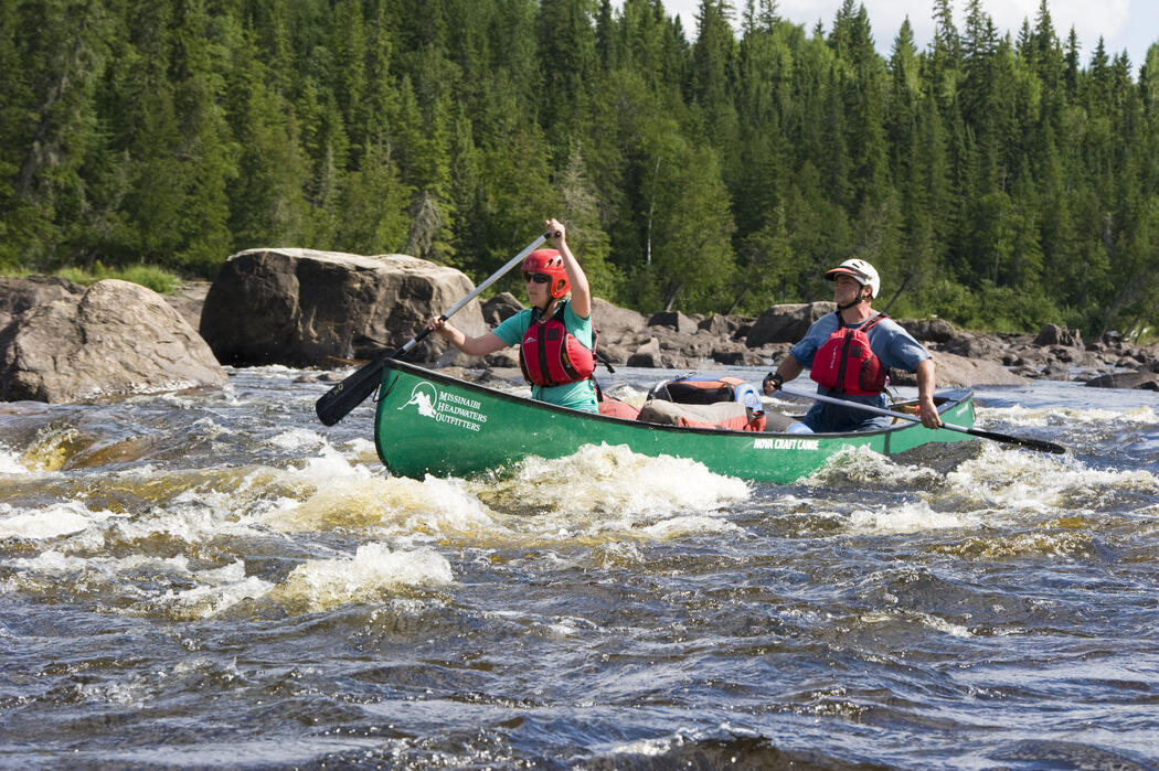 Two people paddling a green canoe on a whitewater river.